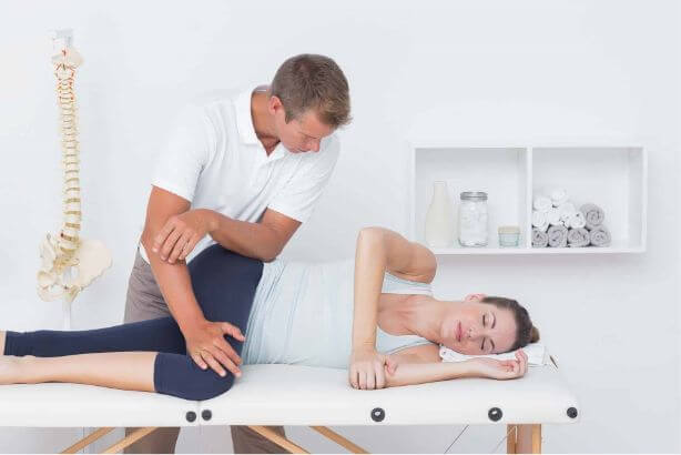 chiropractor doing leg massage to his patient in medical office